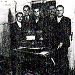 "The Salonica ""cell"" standing behind the wireless radio: from l. to r. are Nicos Oreopoulos, Cosmas Yiapitzoglou, Helias Doundoulakis, and the guards, Nikitas and Stavros."